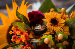 close-up shot of the rings placed on a flower in the bridal bouquet.