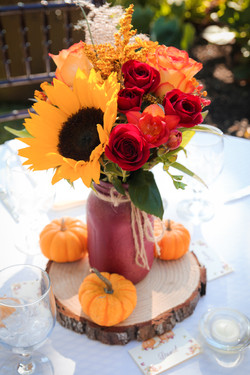 Fall-themed arrangement as reception table centerpiece, with piece of wood and accompanied with mini