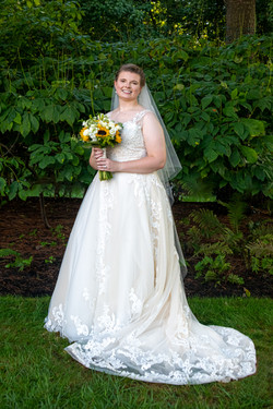 Bride poses with her bouquet in front of green bushes.