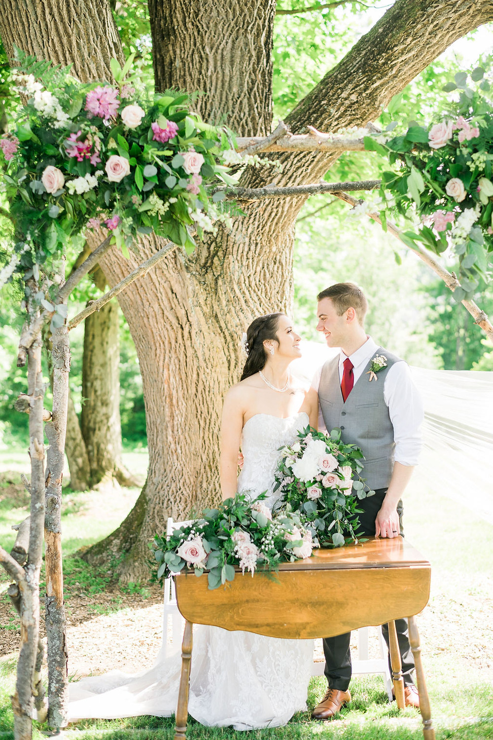 Newlyweds look at each other smiling under their ceremony arbor. Pink & white flowers w/ greenery.