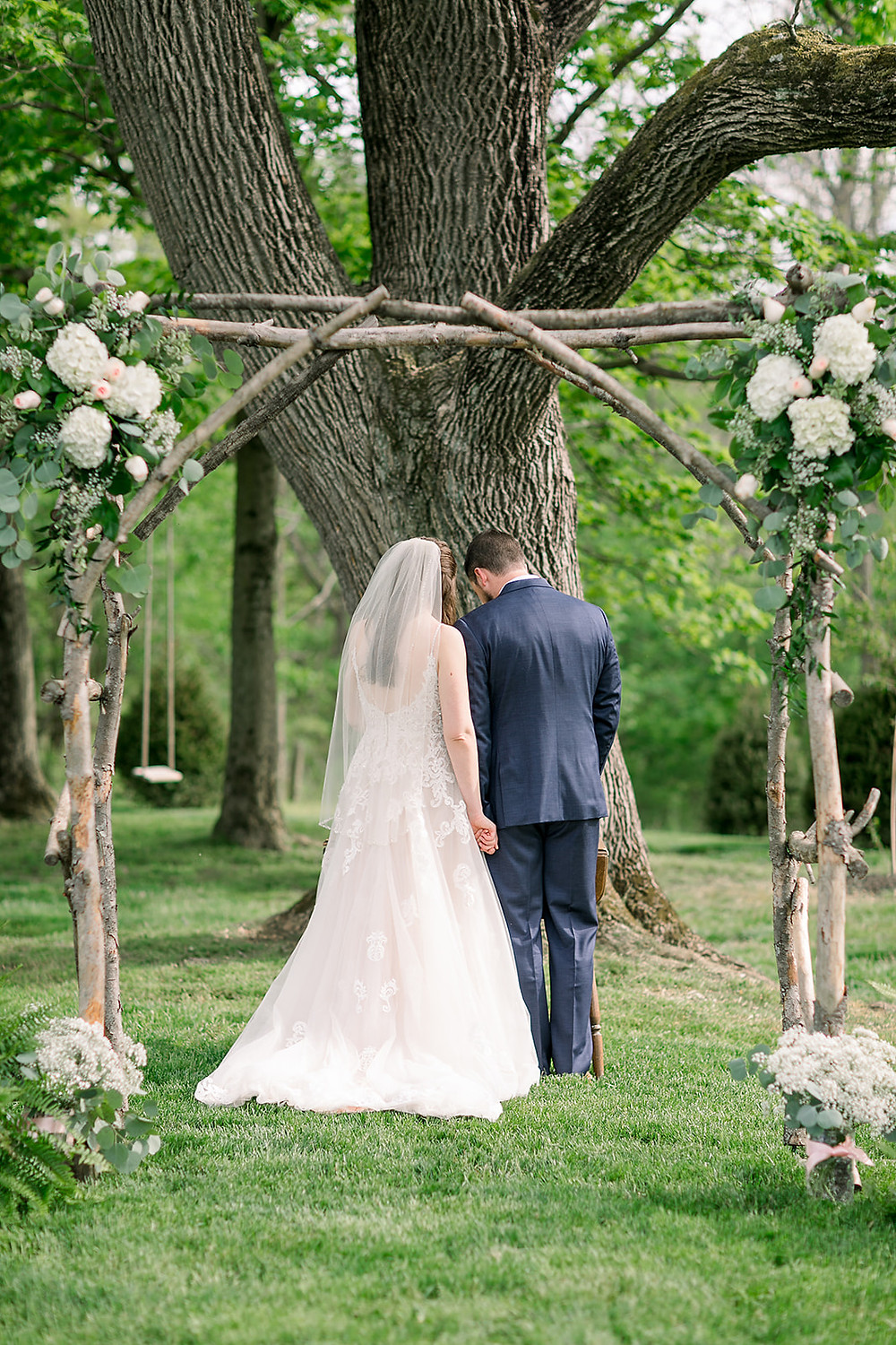 A couple prays together under their ceremony arbor. Green & peach flowers.