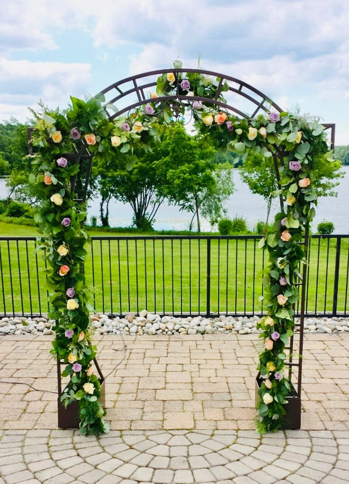 A spring wedding ceremony arbor with purple, yellow, and peach flowers throughout a greenery vine.