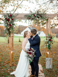 Couple kissing under wedding ceremony arbor - Laura Gares Photography