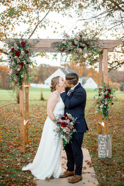 Newlyweds kiss under their ceremony arbor, surrounded by floral arrangements.
