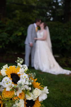 Couple poses in the background blurred, and the bridal bouquet is clear in the foreground.