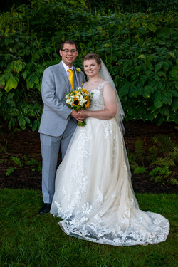 Newlywed couple poses together in front of green bushes.