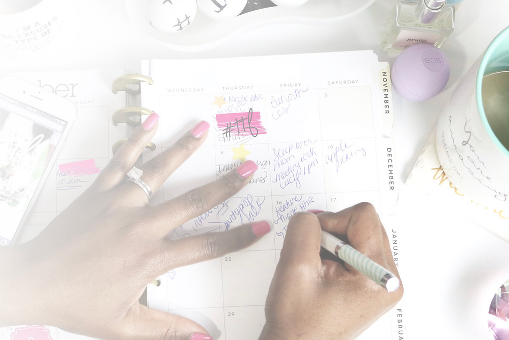 Close-up image of a woman writing in her planner.