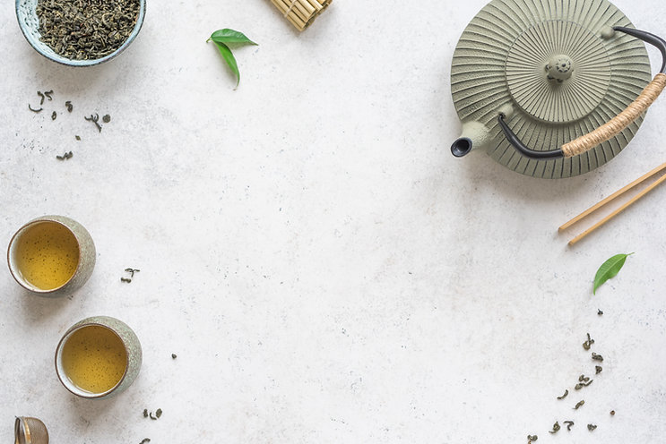 Asian Tea Set -  iron teapot and ceramic teacups with green tea and leaves. Traditional te
