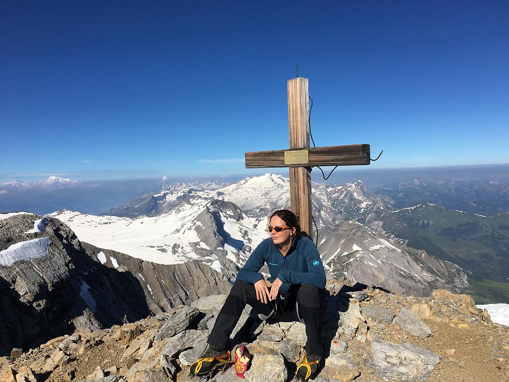 Bergbeklimmer op de top van een berg bij een topkruis