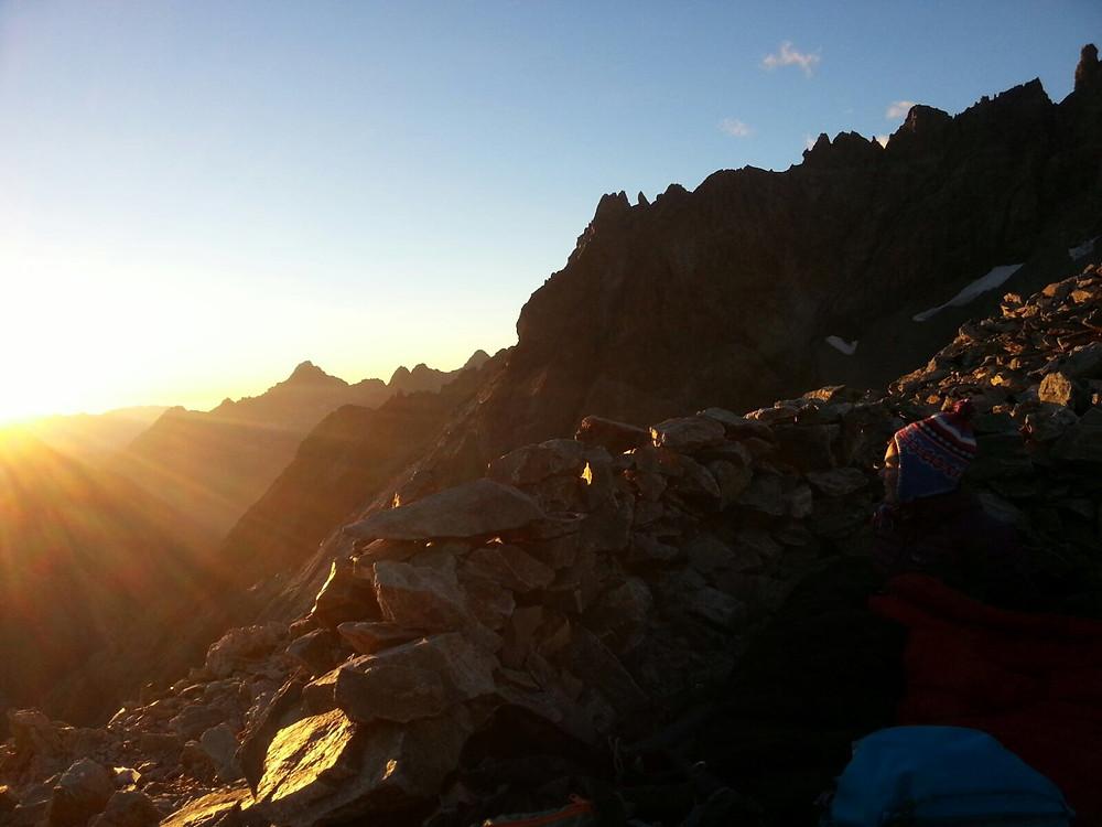 Bergbeklimmer ziet de zon opkomen in de bergen