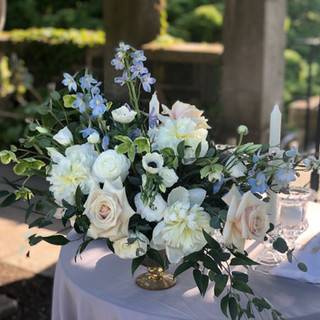Wave Hill wedding centerpiece with cremes baby blues and blush featuring peonies anemone garden roses and delphinium in gold pedestal vase