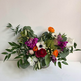 Wild and asymmetrical arrangement with hot orange, pink blooms like orchids and ranunculus with wild greens of olive branch, italian ruscus, and eucalyptus