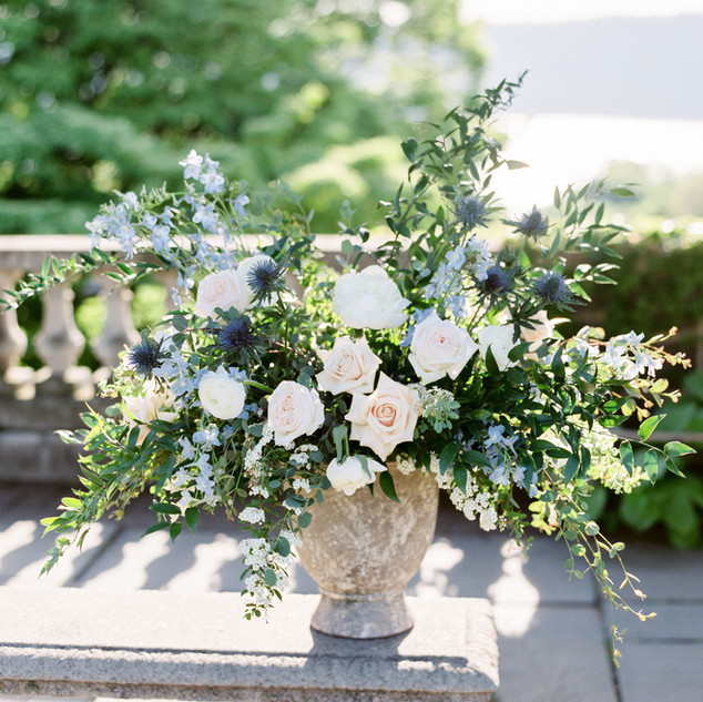 Wave Hill ceremony urn arrangement featuring baby blue delphinium, garden roses, peonies, and blue thistle