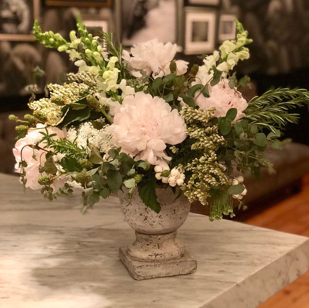 Creamy blooms including peonies, snap dragons, and andromeda in garden stone urn vase for 501 Union