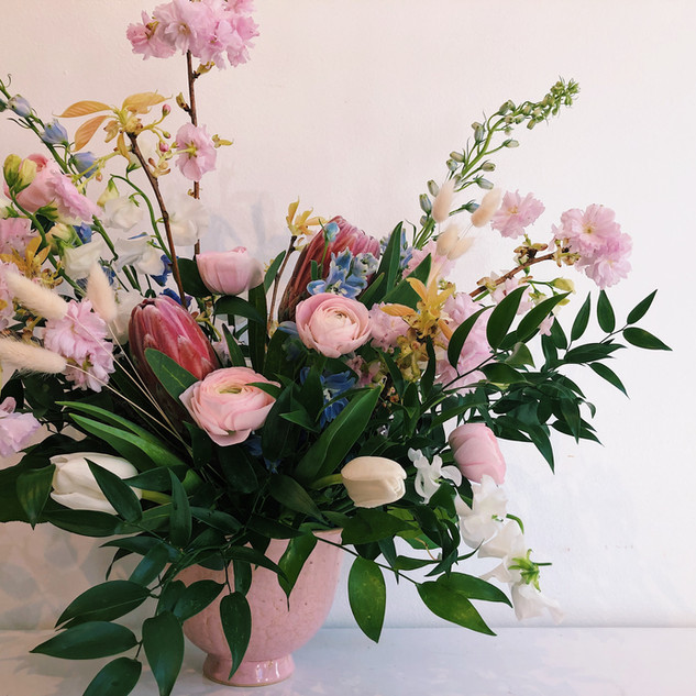 Ikebana inspired gold and pink arrangement with tulips ranunculus sweet pea delphinium and cherry blossom