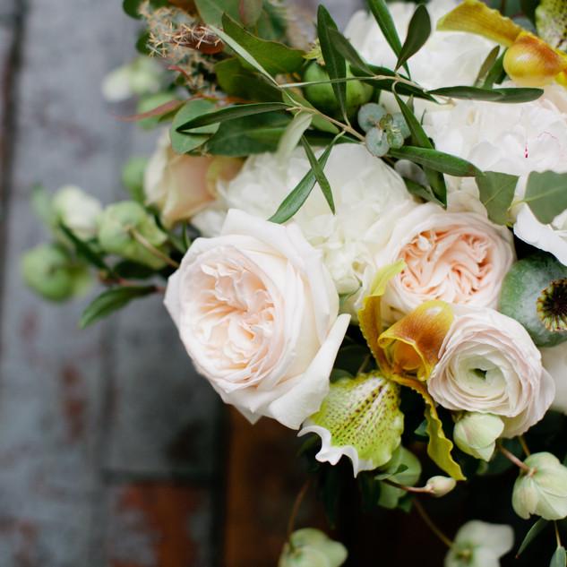 White ohara garden roses, ranunculus, poppy pods, lady slipper, hellebore, and pampas grass for Metropolitan Building Wedding Bouquet