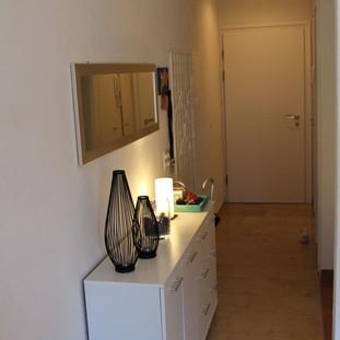 Korridor, Eingangspartie der Wohnung zum Wohnzimmer mit grossem Spiegel und Kommode.