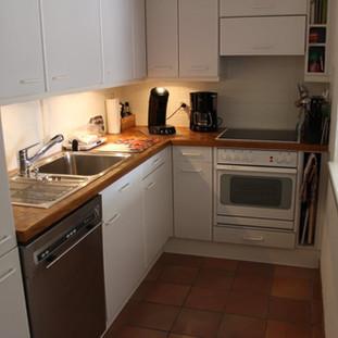Küche mit Kühl- und Gefrierschrank, Glaskeramik Kochherd, Backofen, Kaffee- und Espressomaschine, Wasserkocher, Milchschäumer.