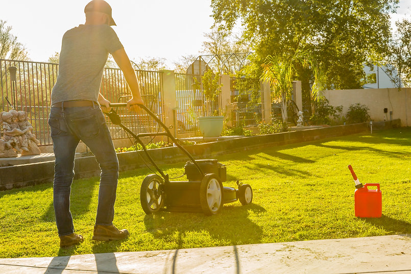 Man mowing lawn with push mower at miday