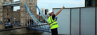 Snagging inspection of One Tower Bridge London - roof top view of a snagging inspector wearing a helmet and a high visible jacket, holding a tablet computer pointing at snagging issue.