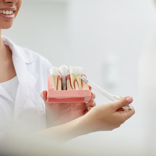 smiling-dentist-pointing-tooth-model.jpg