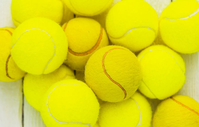 heap-green-tennis-balls-wooden-table.jpg