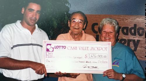 Jon Mullett at the Colorado Lottery presents 1.6 million dollar check to lotto winners