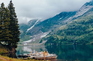 brown wooden boat on lake near green trees and mountains during daytime_edited.jpg