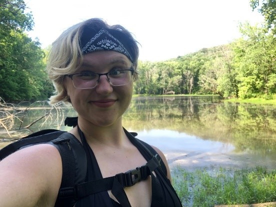 Mae standing in front of a lake