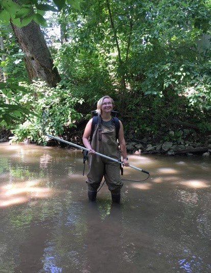 Mae standing in stream wearing electrofishing backpack