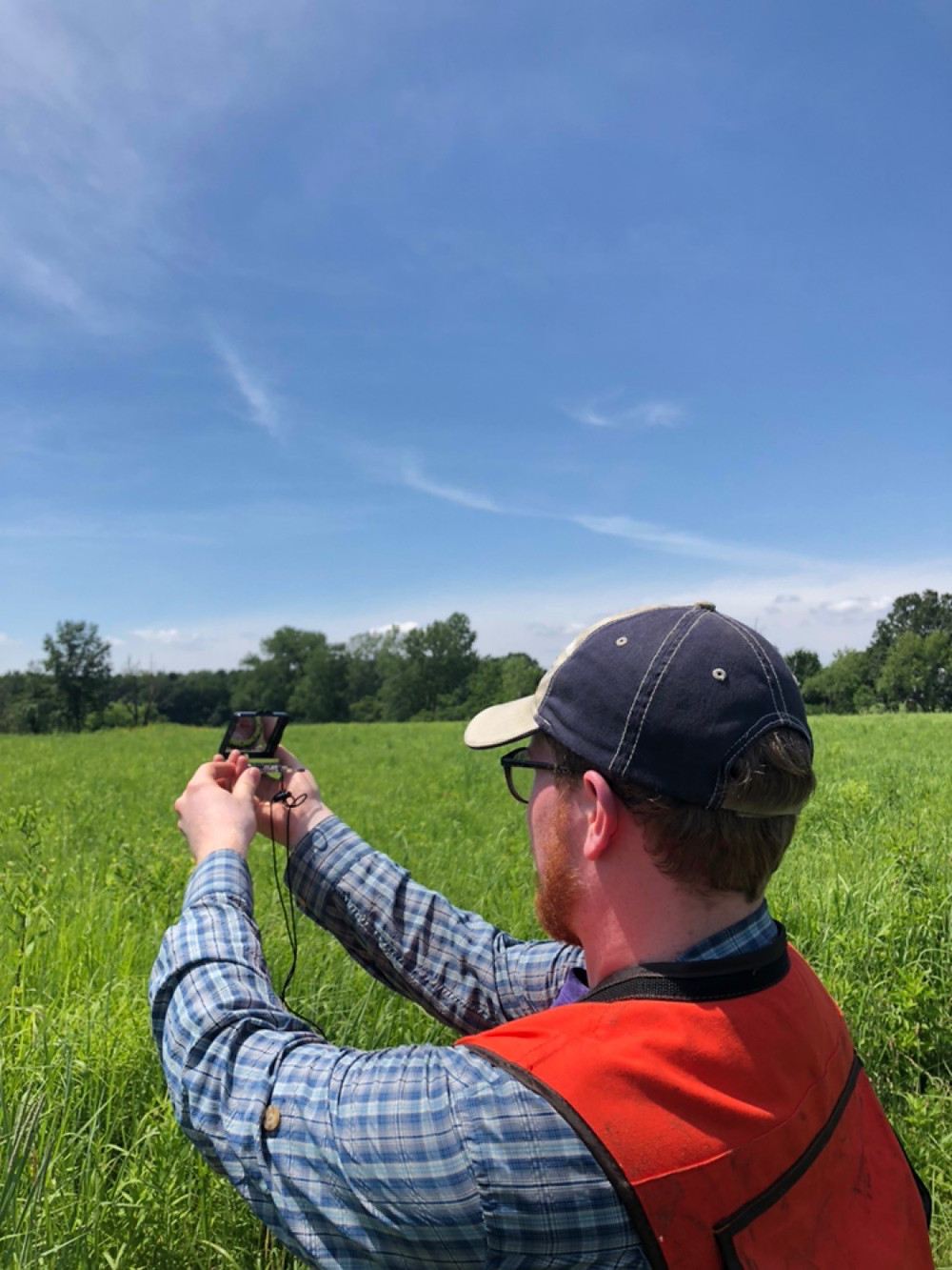 Garret using a compass in the prarie
