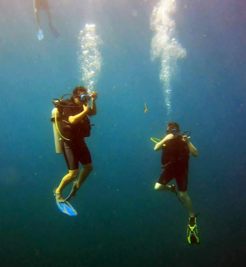 Maggie and friend descending underwater on a SCUBA dive