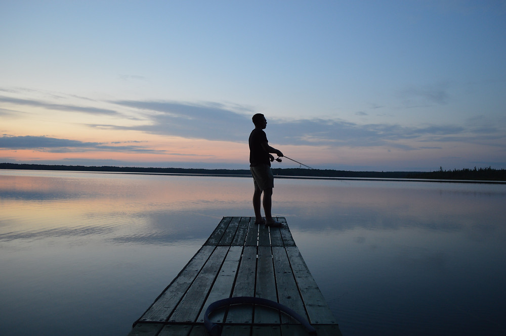 Reece fishing off of pier at sunset
