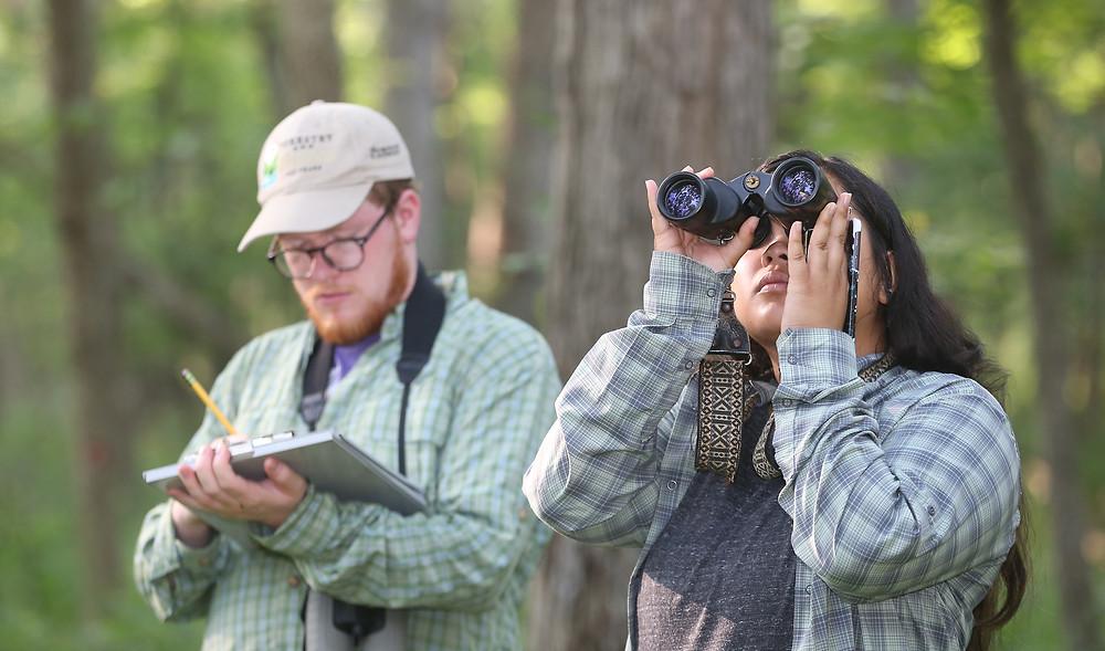 Garret taking notes and Alyssa looking into binoculars