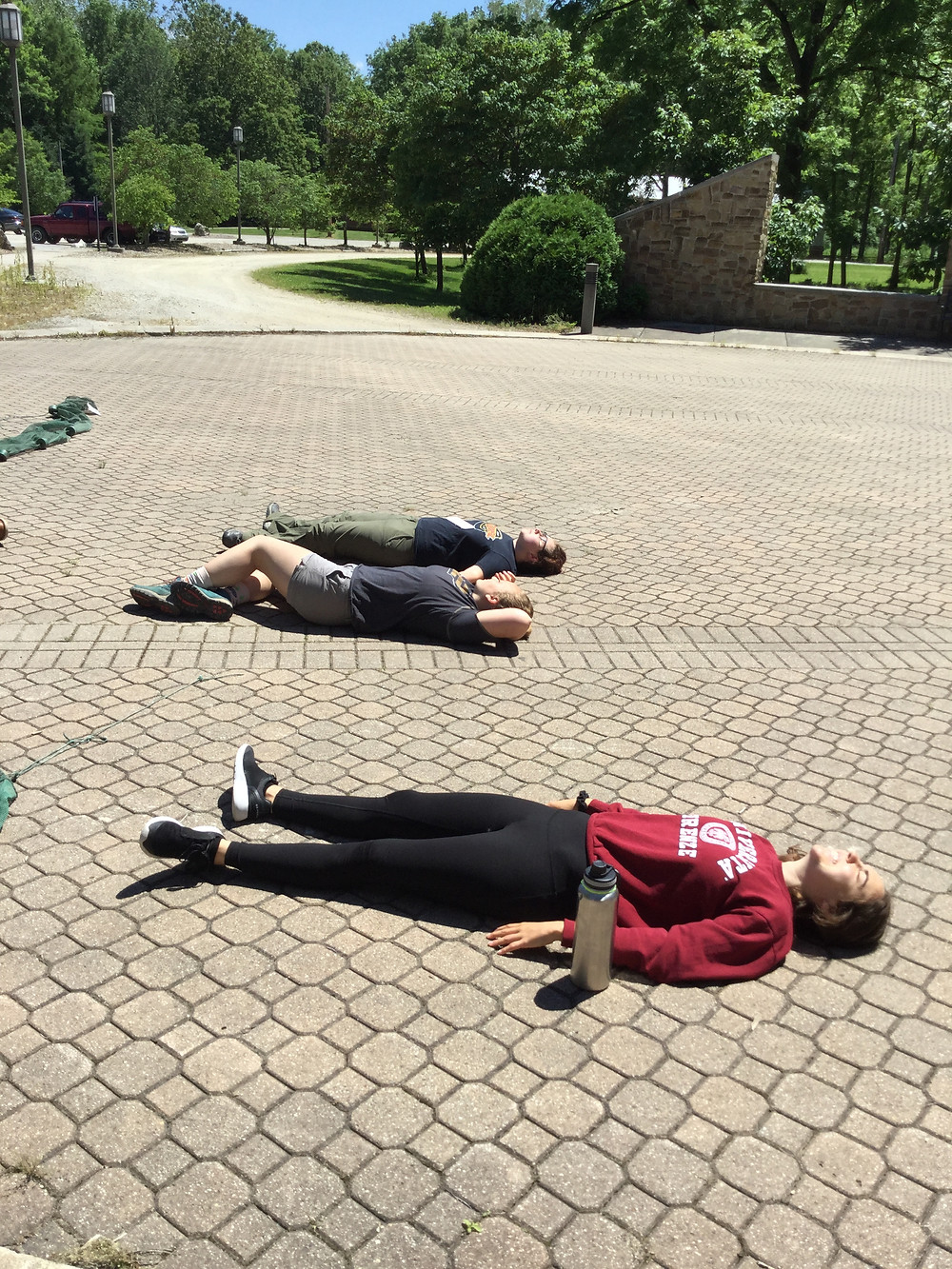 Jenny, Avery and Emily laying on the ground