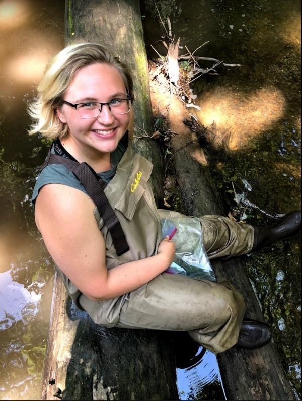 Mae sitting on a fallen log in the stream