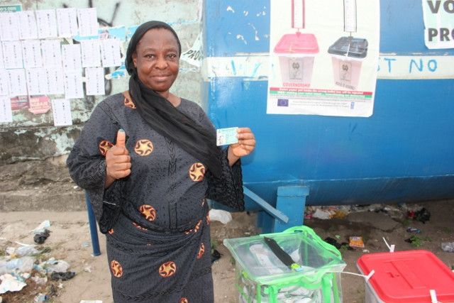 A popular woman leader holding up her thump after casting her ballot