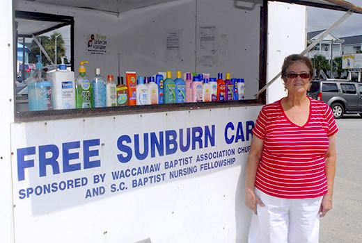 "Martha Bullard stands in front of the ""sunburn trailer"" at Surfside Beach. (Photo courtesy Waccamaw Baptist Association, Conway, SC)"
