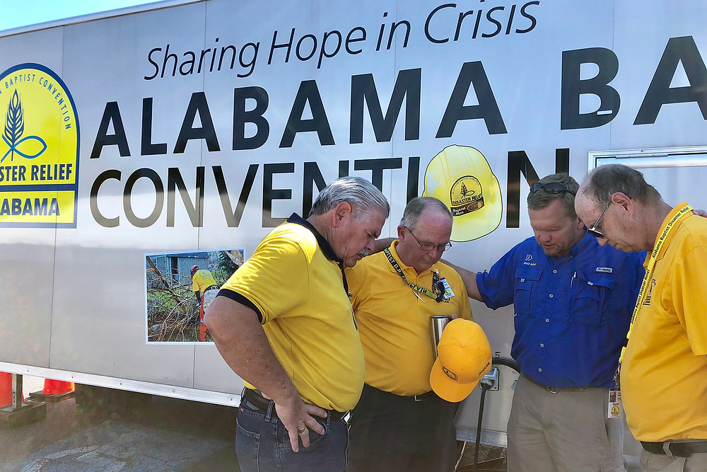 Porter (left), national disaster relief director for the North American Mission Board, and David Melber (second from right), president of NAMB's compassion ministry Send Relief, pray with Mark Wakefield (second from left), disaster relief and chaplaincy ministries strategist for Alabama Baptists, and Alabama DR volunteer David Hendon in Hope Mills, N.C., where Alabama Baptist relief teams have set up their feeding site. (Photo by Brandon Elrod)