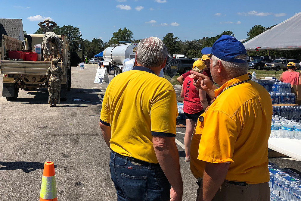 Sam Porter (left gold shirt) and Robert Mabry (right blue cap) look on as National Guard members unload a high-water vehicle to distribute food and supplies to residents in Lumberton, N.C. Porter is the North American Mission Board's national director of disaster relief and Mabry is a volunteer disaster relief leader with the North Carolina Baptist Men. (Photo by Brandon Elrod)