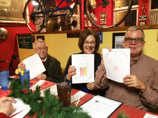 Attendees at the Christmas dinner for widows and widowers of First Baptist Church in Searcy, Ark., show off their artistic efforts during an elf drawing game. (Photo courtesy of Bob and Karen Davis)