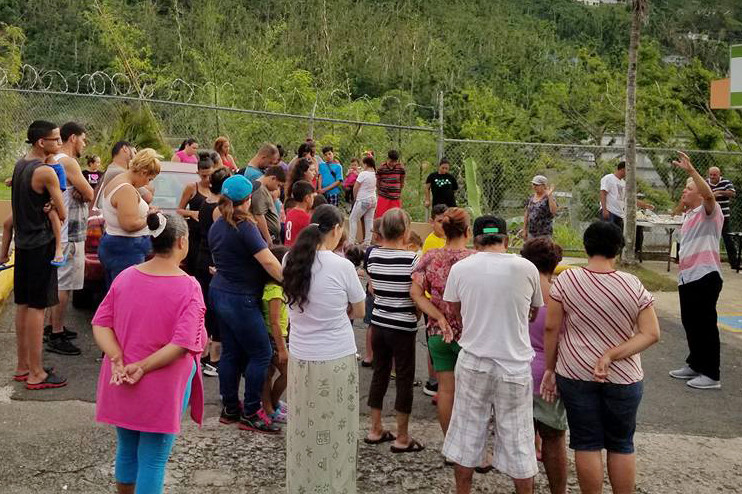 Jorge Santiago preaches to a group of people who gathered in Comerío, Puerto Rico, to share a meal and hear a message from the Bible. Santiago, a missionary with the North American Mission Board, and his family have been ministering in the municipality in the aftermath of Hurricane Maria by providing meals and laundry services. (Photo from Facebook)