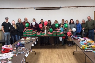 """Members of Tenakee Springs Community Church in Alaska filled 33 Operation Christmas Child boxes in October. Bivocational pastor Todd Buck (right) noted, """"The amazing thing about it is there is no Walmart or Kmart or Target or dollar store or anything like that out there. One gal actually flew to Juneau on a float plane so that she could have stuff to put in two of the boxes. But that's the type of church that they are."""" Pictured (from left) are Calvin Carter, Alice Carter, Jodie Buck, Arnie Strong, Tomi Strong, Cynthia Meyer, Dordie Carter, Debbie Carter, Isabella Strong, Laura Strong, Kirsten Strong, Baly Jones, Mary Heath, Bev Patch and Todd Buck. (Photo submitted)"""