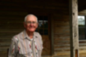 Ellis Brasher stands on the porch of his cypress log home near Rusk, Texas, where he and his wife Irene raise cattle there. (Photo by Gary Ledbetter)