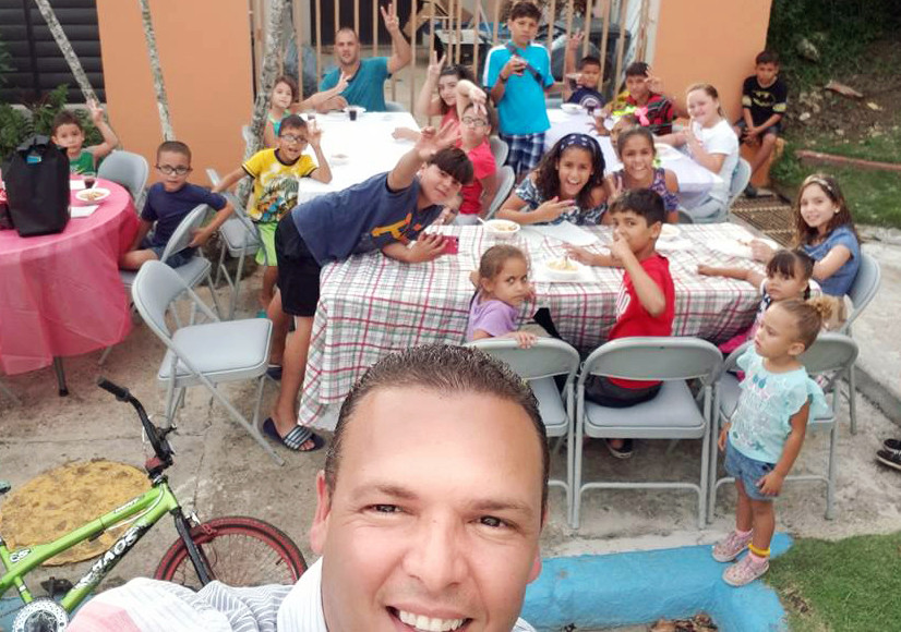 Jorge Santiago poses for a selfie with families as they eat a meal prepared by Santiago, his family and his ministry partners as part of relief efforts in the aftermath of Hurricane Maria. (Photo from Facebook)