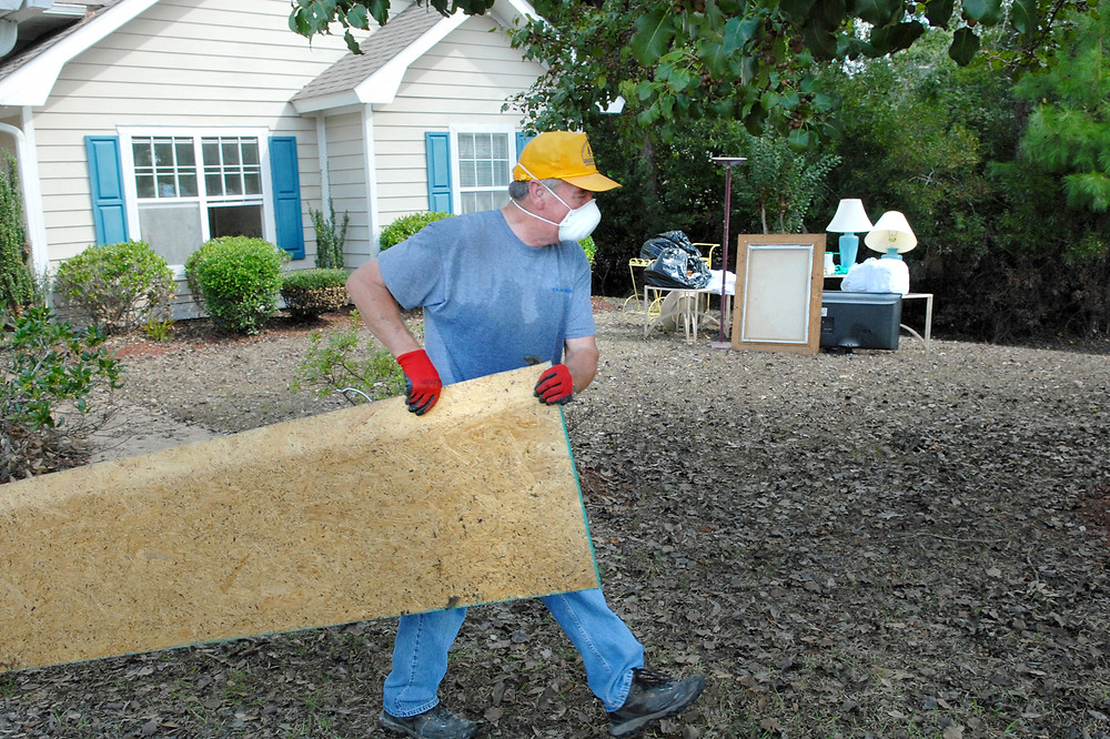 """Lebron Crisp, founding pastor of Living Water Baptist Church, helps take out flood water damaged wood and items from the home of church members Russ and Gerry Frye of Longs, S.C. Crisp called the couple's situation """"heart-breaking"""" and said, """"I want to be out here every waking second."""" (Photo by Laura Sikes/NAMB)"""