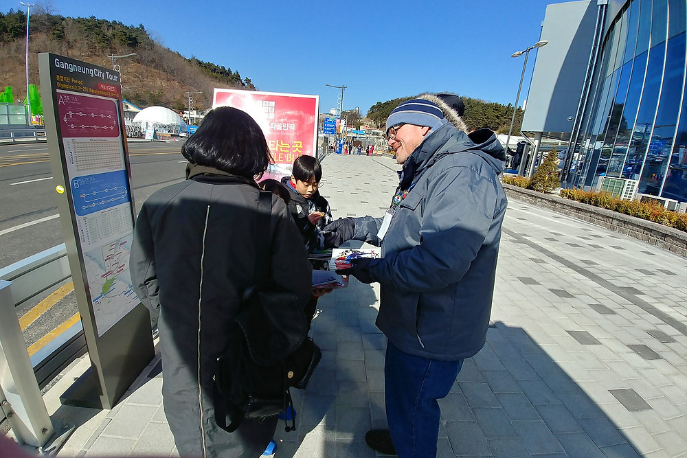 Steve Bradshaw, director of evangelism for the SBC of Virginia, distributes a copy of the book of Romans and John to a South Korean mother at the Gangneung Station. Photo by Tim Ellsworth
