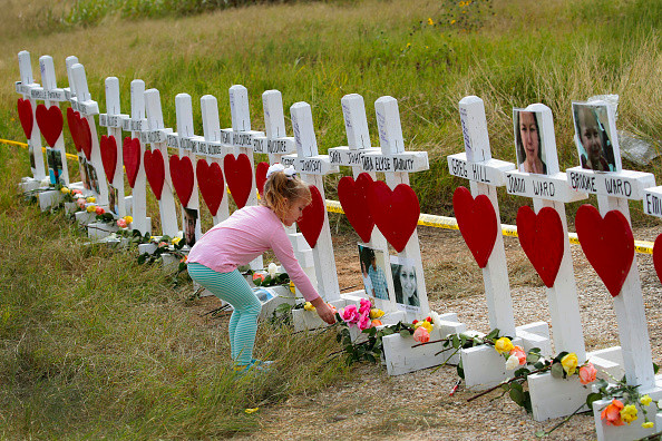 SUTHERLAND SPRINGS, TX - NOVEMBER 09: Four-year-old Shaelyn Gisler leaves a flower at a memorial where 26 crosses were placed to honor the 26 victims killed at the First Baptist Church of Sutherland Springs on November 9, 2017 in Sutherland Springs, Texas. (Photo by Scott Olson/Getty Images)