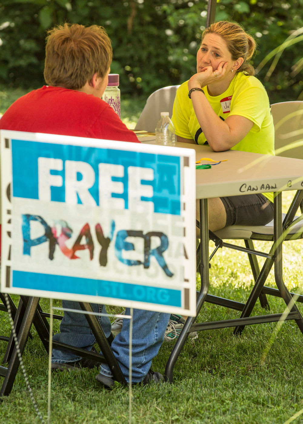 Julie DuVall of First Baptist Church in Bolivar, Mo., takes time to listen to prayer requests from a young man during a block party hosted by Canaan Baptist Church in Imperial, Mo., on Saturday, June 11. The block party was part of Crossover St. Louis 2016, held prior to the annual meeting of the Southern Baptist Convention June 14-15 at America's Center in St. Louis. (Photo courtesy Chris Carter)