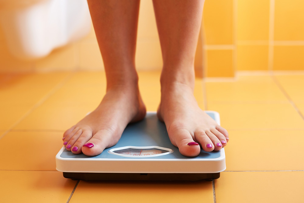 A Pair Of Female Feet On A Bathroom Scale.jpg